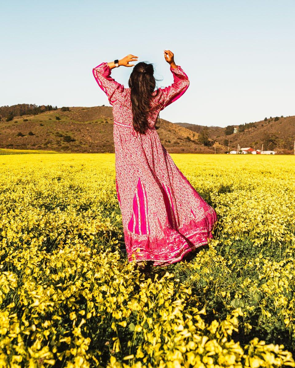 Woman in pink flowy dress standing in yellow wildflower field