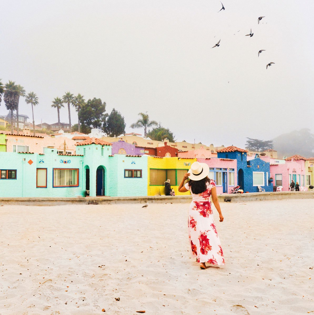 Woman in Capitola beach colorful homes