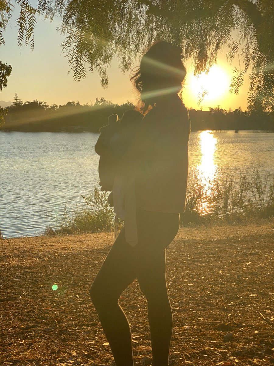woman wearing baby and watching sunset